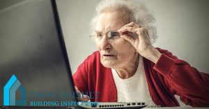 old lady adjusting glasses to read a laptop